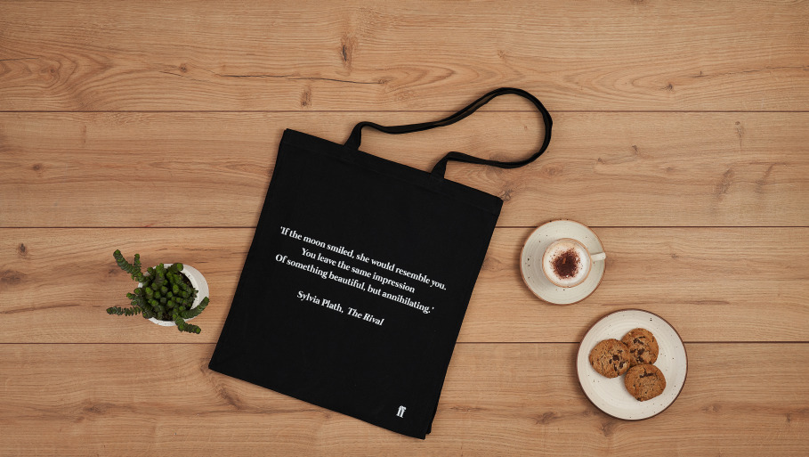 Plath tote bag next to coffee and biscuits